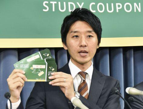「スタディクーポン」を手に記者会見するCFCの今井悠介代表理事=12日午前、文科省