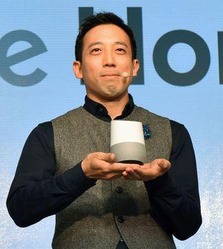 新製品発表会で「グーグルホーム」を手にする関係者=5日午前、東京都港区