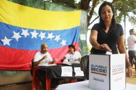 16日、ブラジル・リオデジャネイロで、ベネズエラ野党連合による非公式国民投票に票を投じるベネズエラ人女性(ゲッティ=共同)