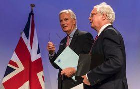 19日、ブリュッセルのEU本部で記者会見したEUのバルニエ首席交渉官(左)と英国のデービス離脱担当相(AP=共同)