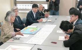 玄海原発再稼働に関し、佐賀県に提出してきた質問に回答がないことに抗議する市民団体のメンバー(左側)=20日、佐賀県庁